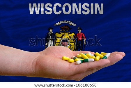 man holding capsules in front of complete wavy american state flag of wisconsin symbolizing health, medicine, cure, vitamins and healthy life - stock photo