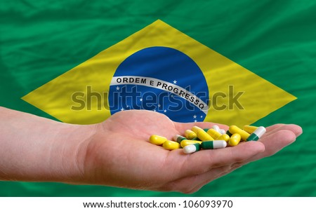 man holding capsules in front of complete wavy national flag of brazil symbolizing health, medicine, cure, vitamines and healthy life