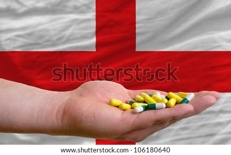 man holding capsules in front of complete wavy national flag of england symbolizing health, medicine, cure, vitamins and healthy life
