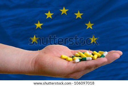 man holding capsules in front of complete wavy national flag of europe symbolizing health, medicine, cure, vitamines and healthy life - stock photo