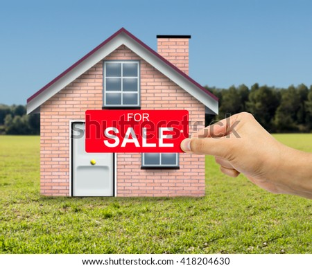 Man holding card home For sale sign red label with percent sign in hand with sale concept and nature house background - stock photo