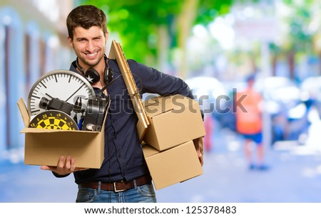 Man Holding Cardboard Box And Picture Frame, Outdoors