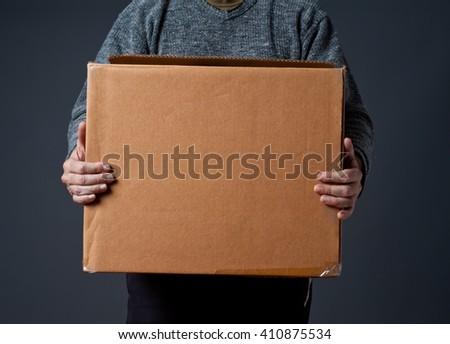 Man holding cardboard box, grey background. - stock photo