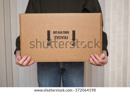 "Man holding cardboard box marked ""fragile, handle with care"" upside down. - stock photo"