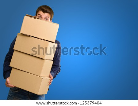 Man holding cardboard boxes on blue background - stock photo