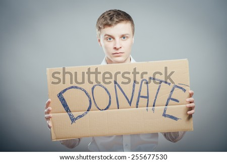 man holding Cardboard text a donate - stock photo