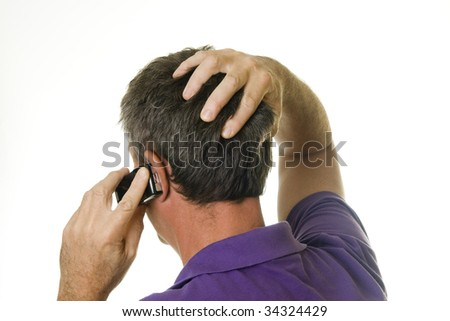 Man holding cell phone and has hand in hair - stock photo