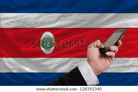 man holding cell phone in front national flag of columbia symbolizing mobile communication and telecommunication - stock photo