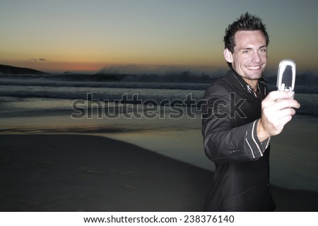Man Holding Cell Phone on Beach at Dusk - stock photo