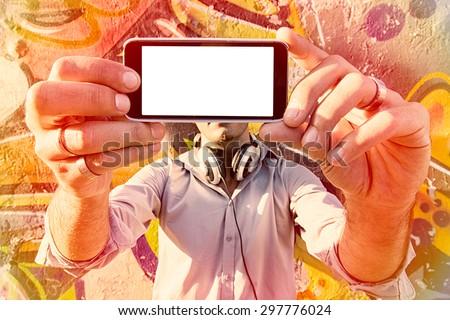Man holding cell phone with blank screen and doing selfie,selective focus  - stock photo