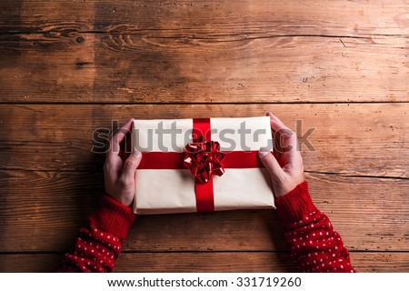 Man holding Christmas present laid on a wooden table background - stock photo