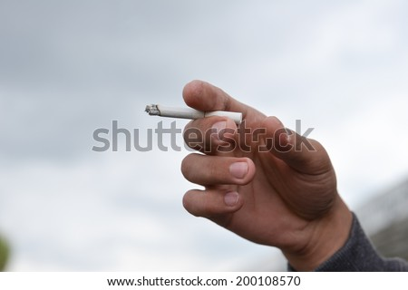 man holding cigarette in his hand closeup outdoor. Cropped shot - stock photo