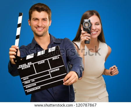 Man Holding Clapper Board And Woman Capturing Photo On Blue Background