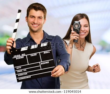 Man Holding Clapper Board And Woman Capturing Photo, Outdoors - stock photo