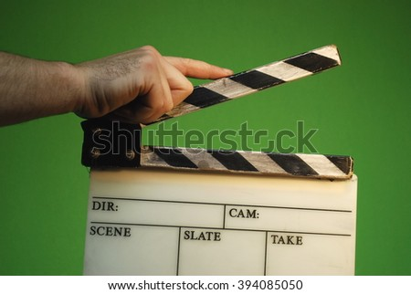 Man holding clapperboard isolated in green - stock photo