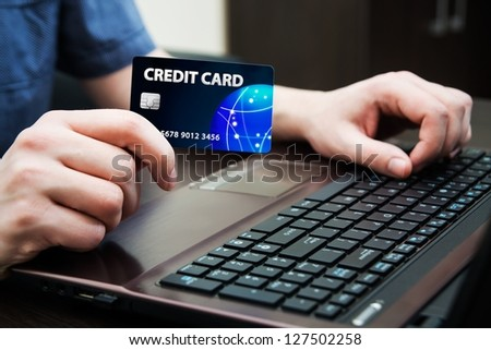 Man holding colorful credit card. Hands on computer keyboard - stock photo