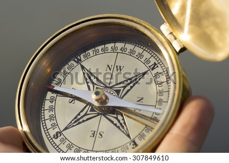 Man holding compass for direction - stock photo
