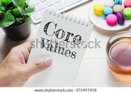 Man holding Core Values message on book and keyboard with a hot cup of tea, macaroon on the table. Can be attributed to your ad. - stock photo