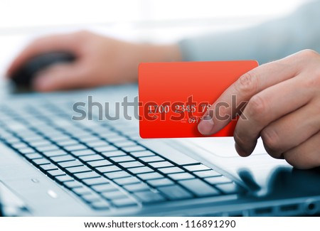 Man holding credit card in hand and entering security code using laptop keyboard - stock photo