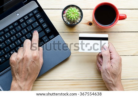 Man holding credit card in hand and entering security code using laptop keyboard.Online shopping concept.Beautiful hand holding credit card.Man using laptop computer on desk table. - stock photo