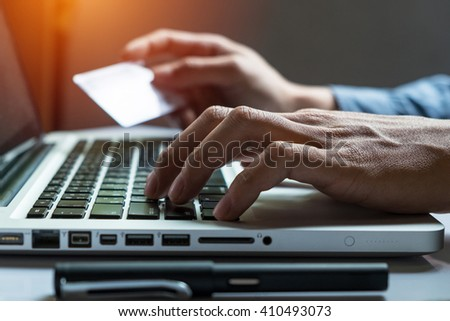 Man holding credit card in hand and entering security code using smart phone on laptop keyboard, online shopping concept.