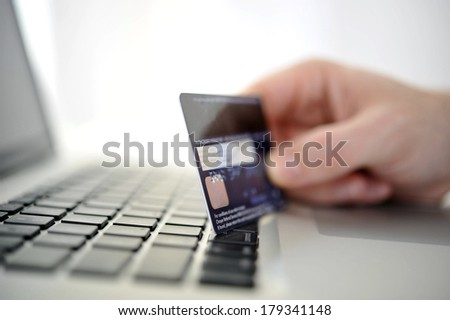 Man holding credit card in hand online shopping and banking with computer - stock photo