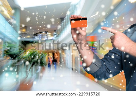 Man holding credit card in his hand at shopping mall.  Christmas and holidays concept  - stock photo