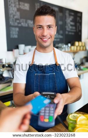 Man holding credit card reader at cafe  - stock photo