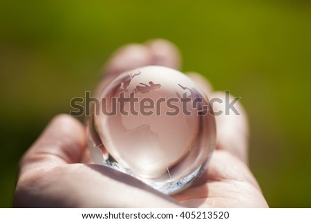 Man holding crystal glass globe model in his hand. Macro photo, shallow depth of field. Concept for care, international affairs, global business - stock photo