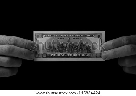 man holding 100 dollar bill on black background - stock photo