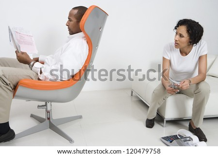 Man holding domestic bills while woman cutting cards at home - stock photo