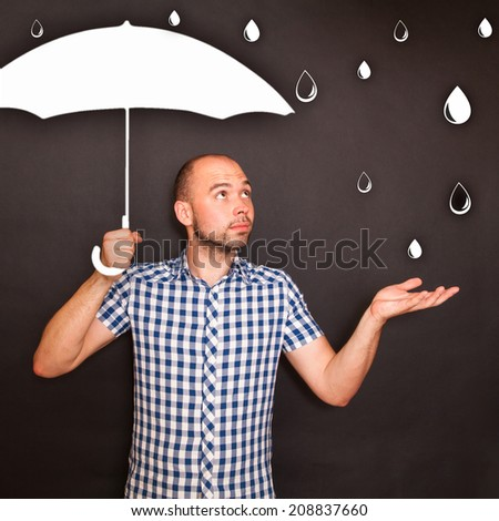 Man holding drawn umbrella in the rain - stock photo