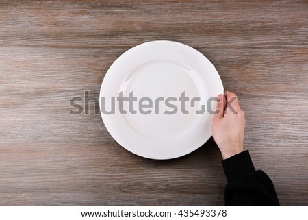Man holding empty plate. Hunger concept - stock photo