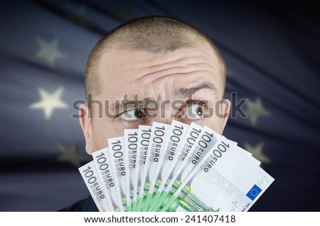 Man holding euro banknotes in front of face - stock photo