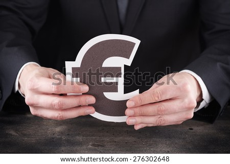 Man holding euro icon in hands on rustic old wooden table