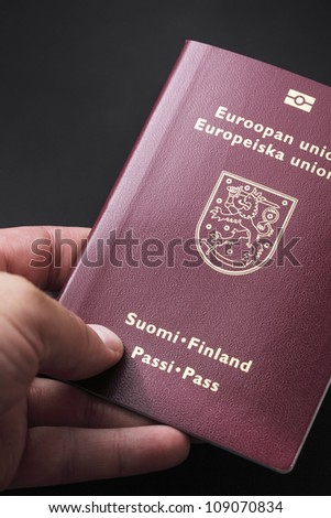 Man holding finnish passport in his hand.