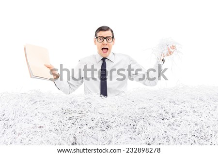 Man holding folder in a pile of shredded paper isolated on white background - stock photo
