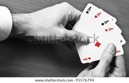 Man holding four aces of a kind