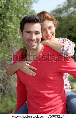 Man holding girlfriend on his back - stock photo