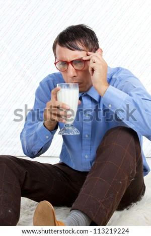 Man holding glass of milk sitting on rug.