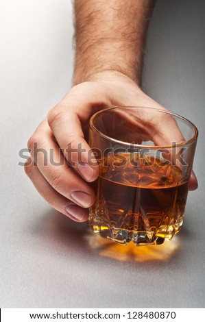 man holding glass of whiskey - stock photo