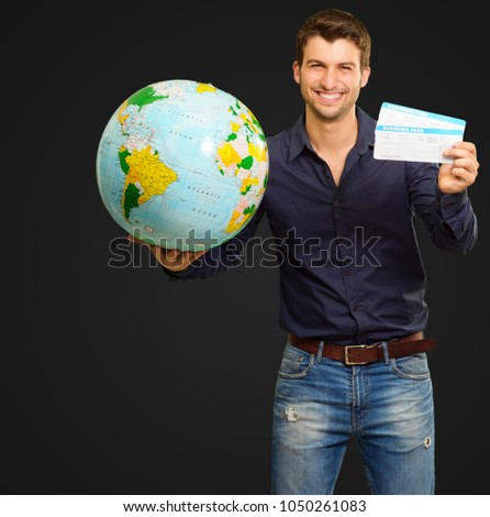 Man Holding Globe And Boarding Pass On Black Background