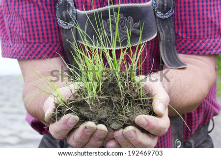 Man holding grass with earth