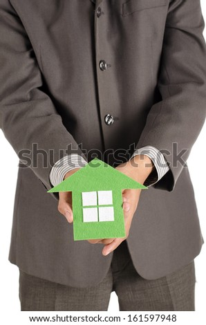 Man holding green paper house - stock photo