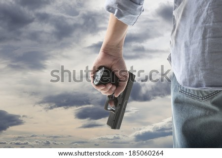 Man Holding Gun against an sky background - stock photo