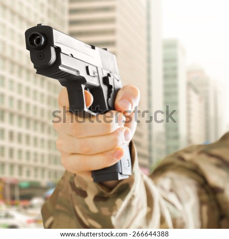 Man holding gun and city on background - stock photo
