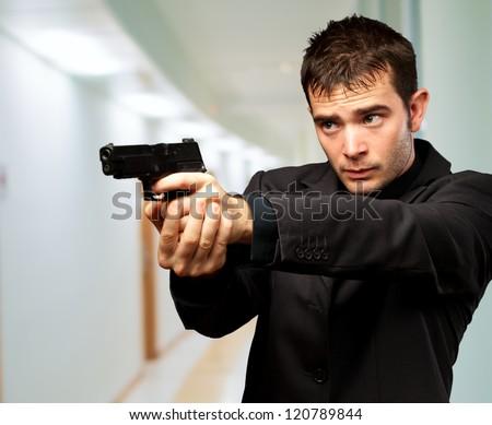 Man Holding Gun, indoor - stock photo