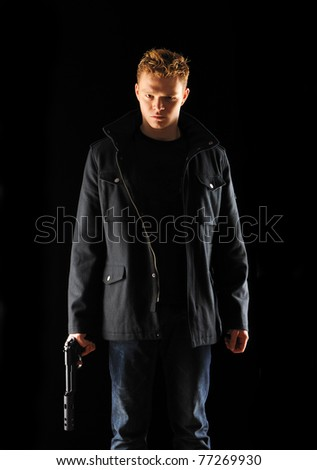 Man holding gun with silencer over black - stock photo