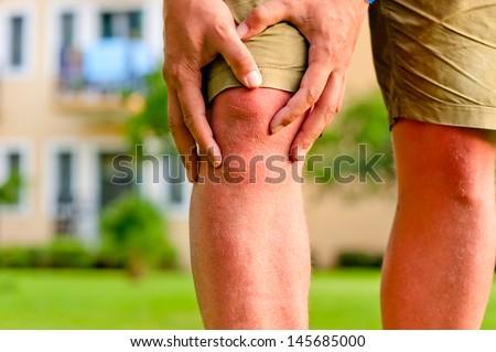 man holding hands sore knee - stock photo