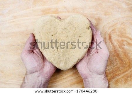 Man holding heart made of pastry in his hands